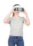 Una ragazza graziosa in cuffia avricolare di VR isolata su un fondo bianco Tecnologie innovarici Un gamer femminile in vetri di u Immagine Stock Libera da Diritti