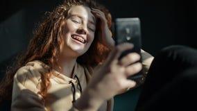 Una ragazza graziosa divertendosi mentre facendo uso dello smartphone archivi video
