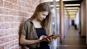 Una ragazza graziosa sorridente dei giovani sta stando contro la parete che tiene una compressa Fotografie Stock Libere da Diritti