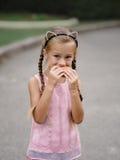 Una ragazza graziosa sta mangiando un cheeseburger su un fondo vago della via Una bambina con un panino Fotografia Stock Libera da Diritti