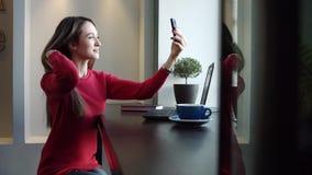 Una ragazza graziosa in un caffè fa un Selfie stock footage