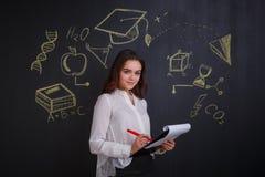 Una ragazza guarda e scrive qualcosa in una cartella con le carte, stanti accanto ad una lavagna Immagine Stock