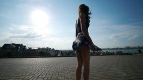 Una ragazza guida un pattino su un quadrato vuoto sui precedenti di bella vista della città stock footage