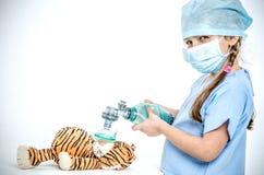 Una ragazza ha vestito nelle tenute chirurgiche di un vestito un ambasciatore sopra una tigre del giocattolo e fa la ventilazione immagini stock