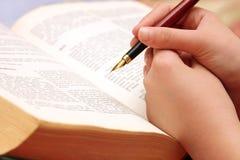 Una ragazza impara da un vecchio libro con la penna a disposizione Immagini Stock Libere da Diritti