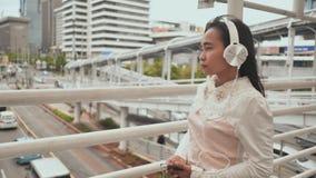 Una ragazza indonesiana triste cammina con la transizione nel centro della città in cuffie bianche ed ascolta musica video d archivio