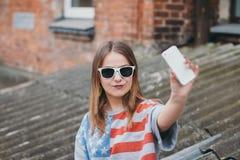 Una ragazza la più hippest in un vecchio cortile con un telefono fa un selfie Immagine Stock Libera da Diritti