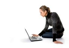Una ragazza lavora con il computer portatile che si siede sul pavimento Fotografia Stock Libera da Diritti