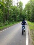 Una ragazza in una maglia con cappuccio guida una bicicletta su un percorso di asfalto fotografia stock