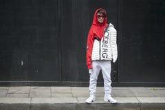 Una ragazza in una maglia con cappuccio rossa, in vetri ed in un iceberg della ditta del rivestimento di sport di bianco posa dav Immagine Stock