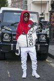 Una ragazza in una maglia con cappuccio rossa, in vetri ed in un iceberg della ditta del rivestimento di sport di bianco posa dav Fotografia Stock Libera da Diritti