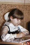 Una ragazza minore sconosciuta ad uno scrittorio scrive qualcosa in un taccuino Fotografia Stock