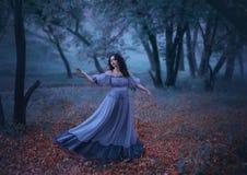 Una ragazza misteriosa con capelli scuri ondulati sta ballando da solo sulle foglie di autunno cadute in una foresta triste di no fotografia stock