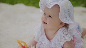 Una ragazza molto piccola e bella che gioca sul copriletto nel parco archivi video