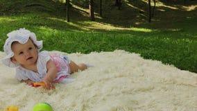 Una ragazza molto piccola e bella che gioca sul copriletto nel parco stock footage