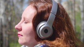 Una ragazza nel parco che ascolta la musica in cuffie Una donna cammina attraverso il parco della molla e gode della musica archivi video