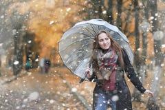 Una ragazza nel parco nelle prime precipitazioni nevose immagine stock