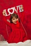 Una ragazza nel rosso che tiene un segno di amore Fotografia Stock