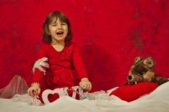 Una ragazza nel rosso che tiene un segno di amore Immagine Stock