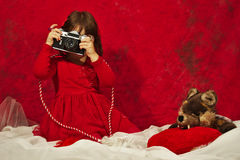 Una ragazza nel rosso facendo uso di una macchina fotografica d'annata della foto Immagine Stock Libera da Diritti