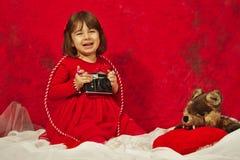 Una ragazza nel rosso facendo uso di una macchina fotografica d'annata della foto Immagine Stock