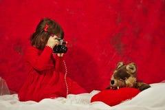 Una ragazza nel rosso facendo uso di una macchina fotografica d'annata della foto Fotografia Stock