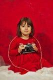 Una ragazza nel rosso facendo uso di una macchina fotografica d'annata della foto Fotografia Stock Libera da Diritti