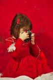 Una ragazza nel rosso facendo uso di una macchina fotografica d'annata della foto Fotografie Stock