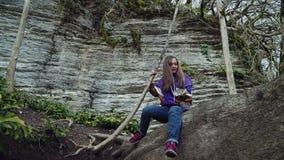 Una ragazza nell'abbigliamento casual scala un albero caduto spesso e si siede su contro lo sfondo della montagna video d archivio