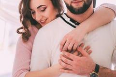 Una ragazza nell'amore abbraccia un uomo da dietro Fotografie Stock