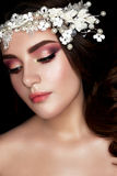 Una ragazza nell'immagine di una sposa con una corona floreale sulla suoi testa e riccioli Un bello modello con un trucco e un pe Fotografie Stock