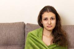 Una ragazza nella disperazione si siede su un sofà beige Sguardo aggrottante le sopracciglia capo frustrato della giovane donna i Fotografia Stock Libera da Diritti