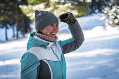 Una ragazza nella foresta dell'inverno esamina la distanza che solleva una mano al fronte immagine stock