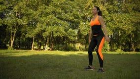 Una ragazza nella foresta si impegna nella forma fisica, facente un esercizio per l'allenamento della gamba video d archivio