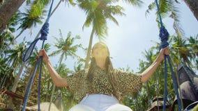 Una ragazza oscilla su un'oscillazione e sugli sguardi al tramonto su una spiaggia tropicale Libertà, resto, vacanza, concetto di archivi video