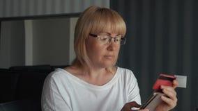 Una ragazza paga un acquisto online Pagamento per gli acquisti online su Internet facendo uso di uno smartphone stock footage
