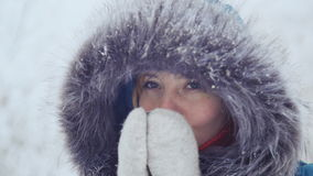 Una ragazza piacevole in guanti beve e si riscalda con tè caldo in un parco dell'inverno archivi video