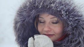 Una ragazza piacevole in guanti beve e si riscalda con tè caldo in un parco dell'inverno stock footage