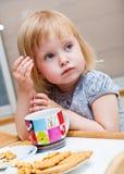 Una ragazza piccola sta mangiando i biscotti fotografia stock
