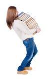 Una ragazza porta un mucchio pesante dei libri Immagini Stock