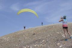 Una ragazza prende un'immagine della gente che vola su un paracadute Bordo di fotografia stock