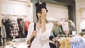 Una ragazza prova sopra un cappello in un deposito davanti allo specchio video d archivio