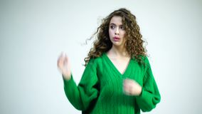 Una ragazza riccia in un maglione verde che balla e che ondeggia i suoi capelli sul dito su un fondo bianco Ragazza parigina nell archivi video