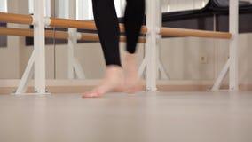 Una ragazza in rivestimento di sport e ghette che ballano in uno stile moderno Movimento al banco, balletto, allungante stock footage