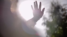 Una ragazza sbalorditiva in un vestito bianco esamina il sole tramite le dita della sua mano Scene divertenti ed emozionali archivi video