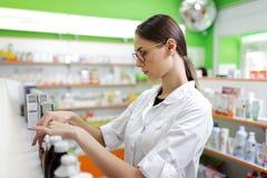 Una ragazza scarna attenta giovanile con capelli scuri lunghi e vetri, portanti un camice medico, sta regolando le medicine sopra immagine stock libera da diritti