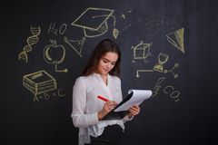 Una ragazza, scrive in una cartella, stante accanto ad una lavagna con un'immagine di scienza e di conoscenza Fotografia Stock Libera da Diritti