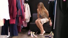 Una ragazza sexy, una donna bionda alta, con le gambe lunghe, bella che prova delle sulle scarpe colorate d'oro su un livello ha  video d archivio