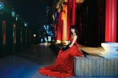 Una ragazza si è vestita in un vestito da sera rosso Immagini Stock Libere da Diritti
