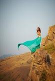 Una ragazza si leva in piedi sul bordo di una scogliera. Immagine Stock